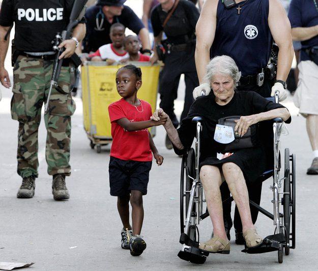 Tanisha Blevin, 5 anos, segura a mão de Nita LaGarde, 105 anos, também vítima do Furacão Katrina, enquanto elas são evacuadas do centro de convenções em Nova Orleans.