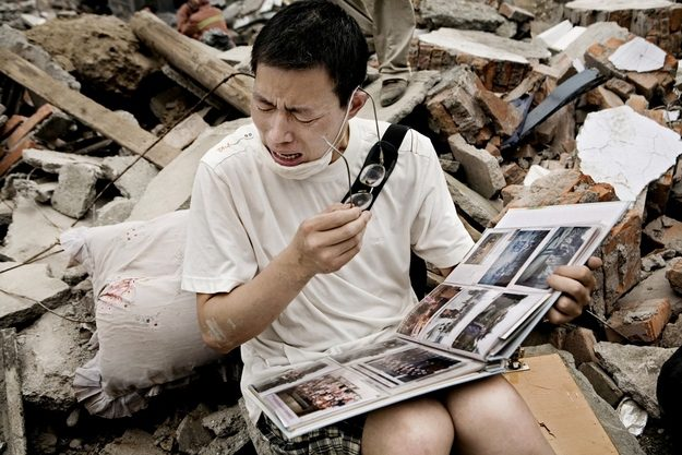 Um sobrevivente encontra um álbum de fotos e memórias preciosas nos restos da sua casa após um terremoto em Sichuan, na China.