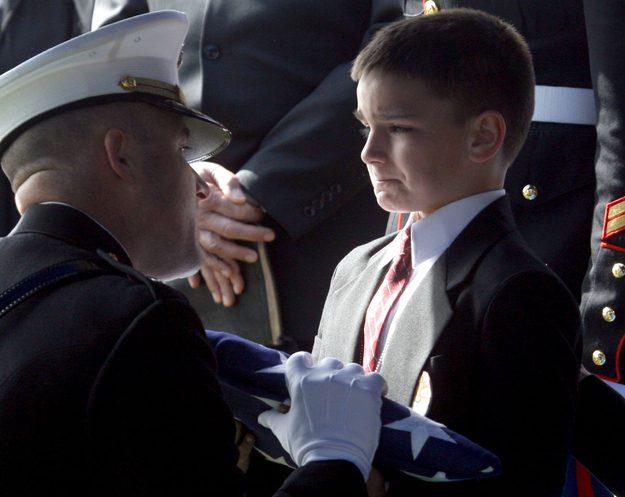 Christian Golczynski de oito anos recebe a bandeira pelo seu pai, o Sargento da Marinha Marc Golczynski, durante uma missa memorial.