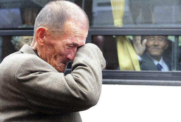 Um homem Norte Coreano acena enquanto um parente Sul Coreano chora.