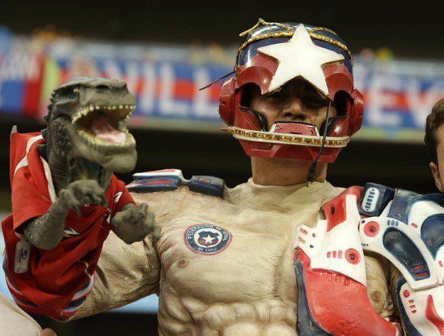 3° lugar: este torcedor chileno com uma fantasia de um super herói segurando um dinossauro.