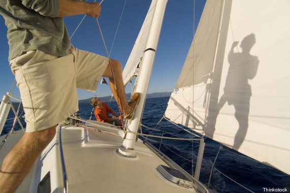 Low section view of a man pulling a rope on a sailboat