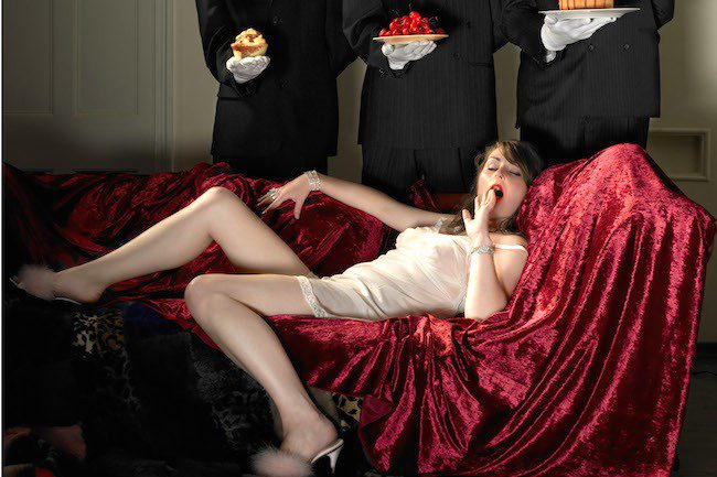 Young woman reclining in negligee with three buttlers waiting to serve her