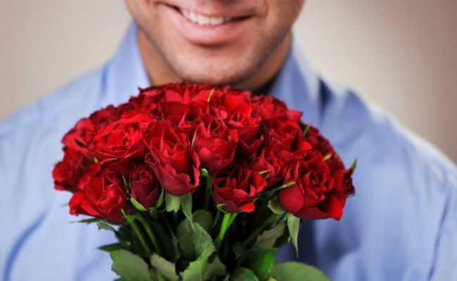 Homem rindo com buquê de flores