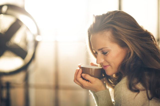 Close-up of a brunette woman in profile, head and shoulders only, holding and smelling a hot cup of coffee. Industrial chic background.