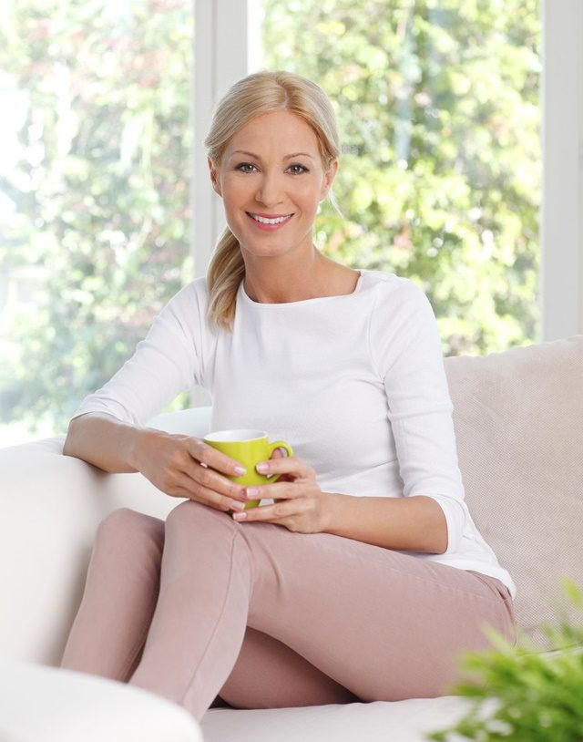 Portrait of beautiful woman sitting at living room at sofa and holding hand a cup of tea while looking at camera and smiling.