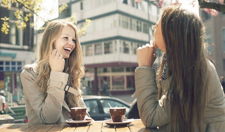 Two young women talk and drink coffee in cafe, outdoors