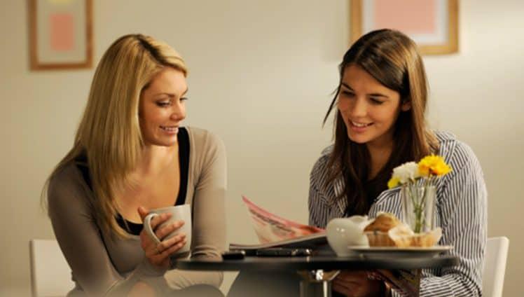 girls reading magazine in coffee shop