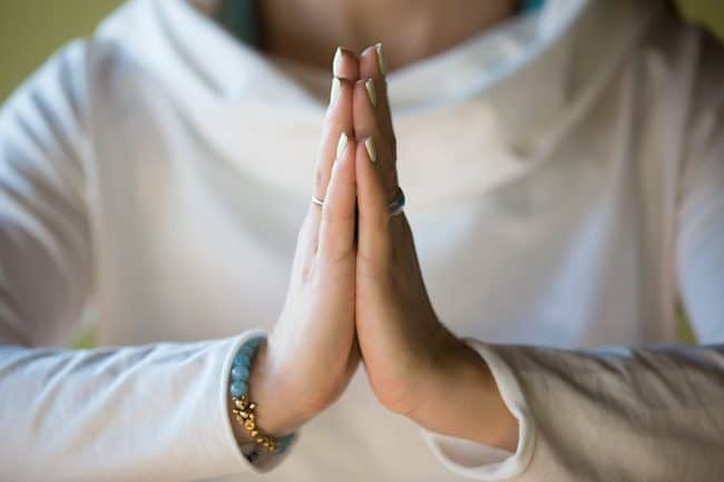 Close-up of hands of sporty young beautiful woman in white clothes meditating indoors focus on arms in Namaste gesture ** Note: Shallow depth of field