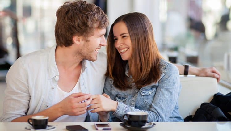 Candid image of young couple smiling in a coffee shop. Shallow DOF, focus on man's eyelash.