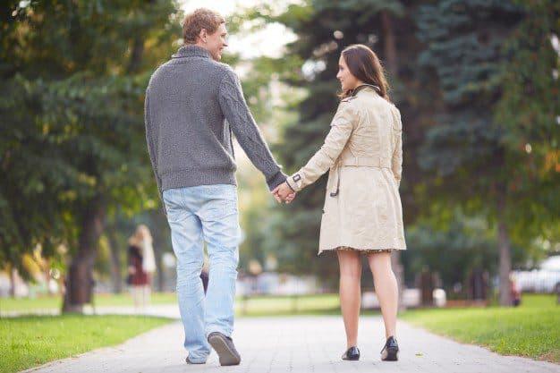 casal-de-maos-dadas-caminhando-para-longe_1098-971