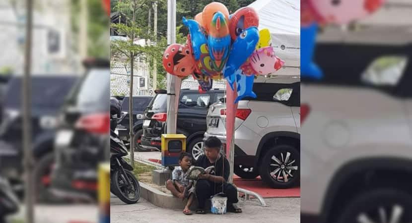 capamenino ensina irmao mais novo a ler enquanto vende baloes na rua Sobrevivem juntos
