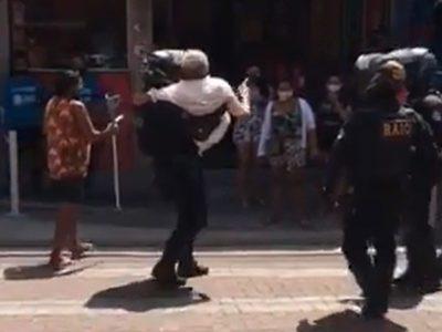 3 capa Para ajudar idoso com dificuldades a atravessar a rua policiais param o transito e o carregam no colo