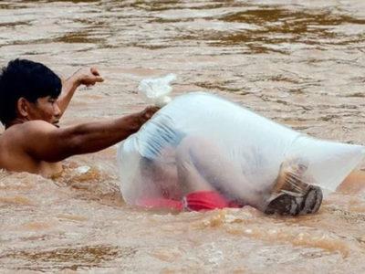 capapais de vila do Vietna atravessam os filhos por rio dentro de sacos plasticos para chegarem a escola